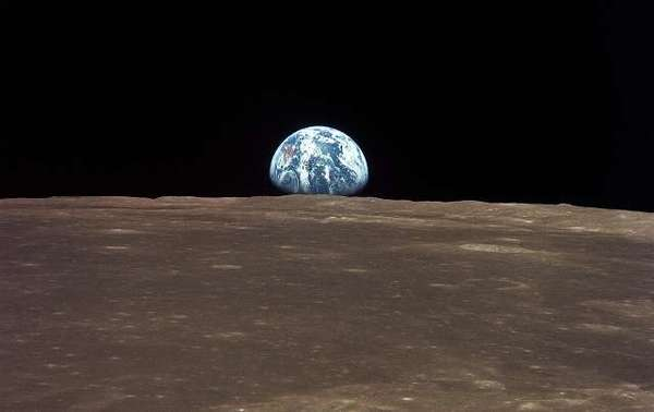 """منظرٌ للأرض من القمر. أُخذت الصّورة من مركبة """"أبولو 11"""" الفضائيّة الموجودة وسط بحرٍ من التّربة القمريّة. المصدر: ناسا"""