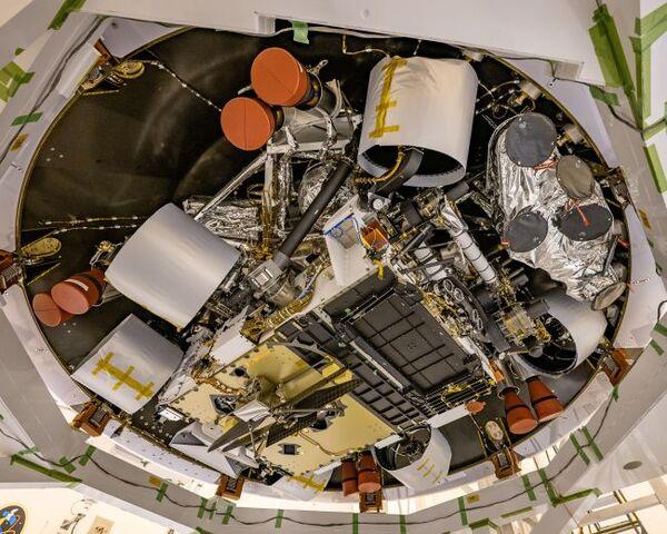 التقطت هذه الصورة في 29 أبريل/نيسان، وهي تظهر الجزء السفلي من مركبة برسفيرنس المريخية الجوالة وطائرة الهيليكوبتر المريخية ''إنجنويتي'' Ingenuity helicopter المتصلة بها (الوسط السفلي للصورة). تمثل الحلقة الخارجية القاعدة التي ترتكز عليها القشرة الخلفية، بينما تكون الأجزاء التي على شكل أجراس و المغلفة باللون الأحمر دعامة لفوهات المحرك في مركبة الهبوط. تم تغليف العجلات بمادة واقية يتم إزالتها قبل الإقلاع. (حقوق الصورة: NASA/JPL-Caltech)