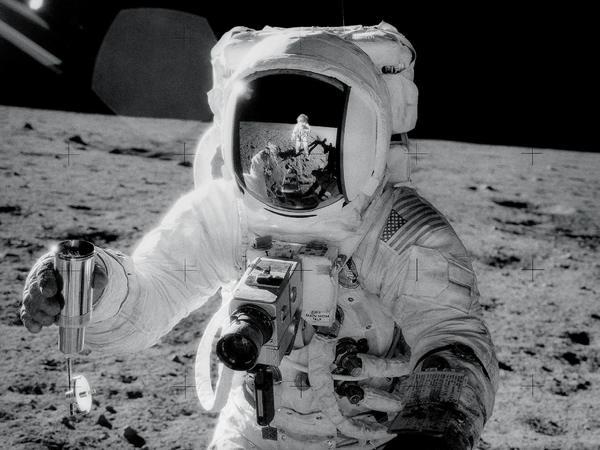 """""""آلان بين"""" يأخذ عيّنة من الثّرى القمريّ خلال مهمة """"أبولو 12"""". المصدر: ناسا"""