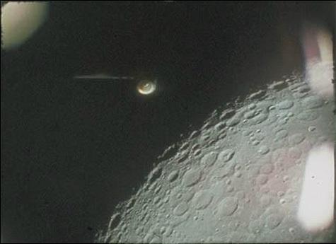 تظهر الصورة لقطة عالية الدقة من الفيلم الذي سُجل في بعثة أبولو 16 للجسم المشكوك في أمره (في منتصف أعلى الصورة) وموقعه بالنسبة للقمر. وتظهر أيضًا الانعكاسات على النافذة (يسار ويمين الصورة). المصدر: NASA