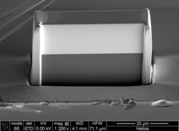 صورة لعدسة الأشعة السينية المبتكرة، وقد صوِّرت باستخدام المجهر الإلكتروني الماسح. بُني الجزء الفاتح باستخدام 5500 طبقة تتناوب بين التنغستن وكربيد السيليكون. أما الجزء أسود اللون فهو الركيزة (substrate). عرض العدسة 40 مايكرومتراً.