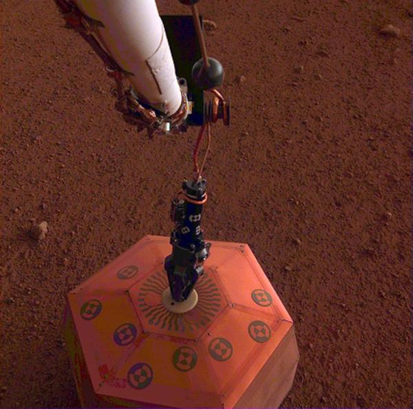 صورة لمقياس الزلازل الخاص بمركبة إنسايت بعد أن وضعته على سطح المريخ في 19 ديسمبر/كانون الأول 2018. وكانت هذه أول مرةٍ يتم فيها نشر أداةٍ علمية مباشرة ًعلى سطح الكوكب الأحمر. حقوق الصورة: NASA/JPL-Caltech