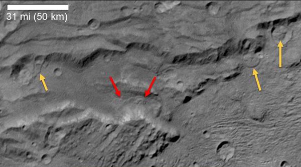 """رصد العلماء من بعثة نيوهورايزنز التابعة لناسا علامات انهيارات أرضية طويلة ماضية على أكبر قمر تابع لبلوتو """"شارون"""". سميت هذه الصورة بشكل غير رسمي بفتحة السكون Serenity Chasma، التقطتها كاميرا الاستطلاع بعيد المدى لنيوهورايزنز LORRI في 14 تموز/يوليو 2015، من مسافة تبلغ 48,912 ميلاً (78,717 كم). وتشير الأسهم في الصورة إلى دلائل على نشاط انهيار أرضي.  حقوق الصورة: NASA/JHUAPL/SwRI."""