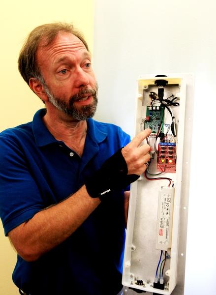 """يوضح الباحث الرئيسي الدكتور هولبيرت أن نموذج جهاز الإضاءة الذي تم تطويره في منشأة Swamp Works التابعة لمركز كنيدي، مصنوع أساساً من قطع مصنعة جاهزة ومتاحة بسهولة. يشير هولبيرت في الصورة إلى واحدة من اللوحات الكهربائية في جهاز الإضاءة التي تم تطويرها في قاعدة فلوريدا لإطلاق المركبات الفضائية. يقول هولبيرت: """"إذا استطعنا جعل هذه التكنولوجيا جديرةً بالاهتمام، يمكن أن تصبح من التقنيات القيِّمة جداً في المستقبل"""". المصدر: NASA/Kim Shiflett"""