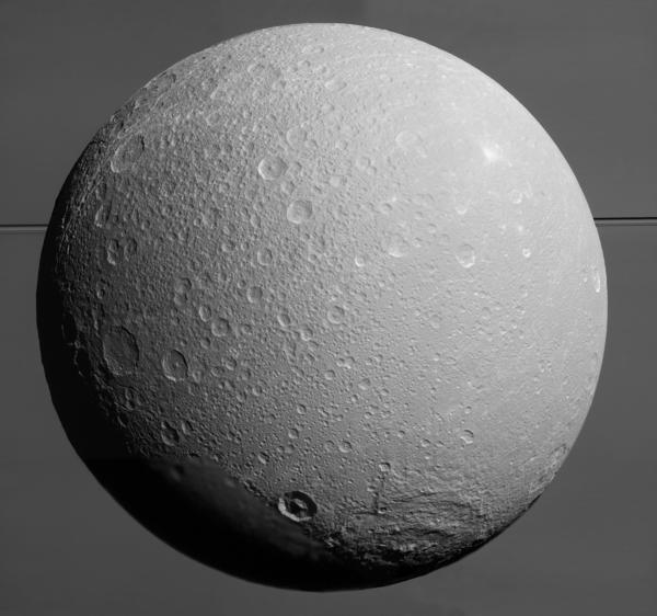 """التُقطت هذه الصورة لقمر زحل المتجمد """"ديوني"""" بواسطة مركبة كاسيني التابعة لناسا، ويظهر زحل العملاق مع حلقاته في خلفية الصورة. وقد التقطت قبل الاقتراب الأخير للمهمة من القمر في 17 أغسطس/آب عام 2015.    Credit: NASA / JPL-معهد كاليفورنيا للتكنولوجيا / معهد علوم الفضاء"""