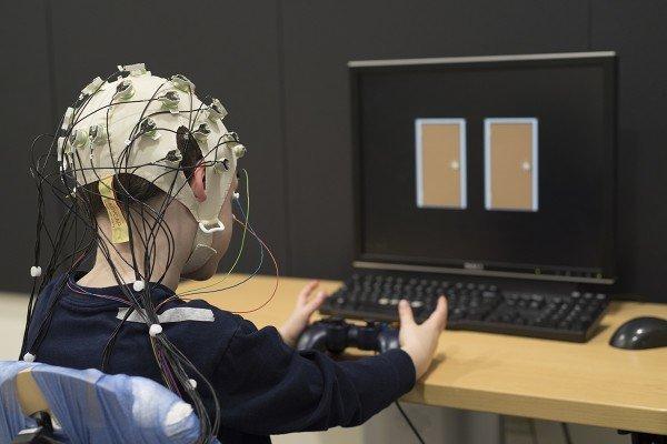 طفل يرتدي الجهاز الذي يقيس النشاط الكهربائي في الدماغ وهو يختار أَحَدَ بابين على شاشة الكمبيوتر. في حال اختار أحد البابين يفوز بنقطة في حين أن اختياره للباب الأخر ينتج عنه فقدانه للنقاط. وقد وجد الباحثون في جامعة واشنطن أن أدمغة الأطفال الذين يعانون من الاكتئاب لا تتفاعل بالقوة نفسها التي عند الأطفال السليمين للنجاح في هذه اللعبة. حيث إن ردات فعلهم الضعيفة تجاه تلقي المكافأة هي علامة سريرية تدل على الاكتئاب. تعود حقوق الصورة إلى: روبرت بوسطنRobert Boston