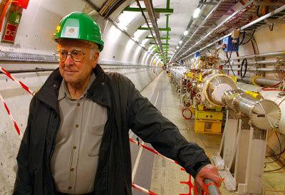 بيتر هيغز Peter Higgs -الشخص الذي سمي جسيم بوزون هيغز باسمه- وهو يتجول في مصادم الهادرونات الكبير.  حقوق الصورة : Alan Walker/AFP/GettyImages .