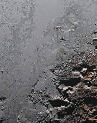 """التقطت المركبة الفضائية """"نيو هورايزنز"""" New Horizons التابعة لناسا، هذه الصورة المثيرة التي تُظهر المرتفعات الوعرة والمظلمة المدعوّة """"كرون ماكولا"""" Krun Macula (في أسفل اليمين)، والتي تقع على الحدود مع مجموعة من السهول الجليدية لبلوتو. Credits: NASA/JHUAPL/SwRI"""