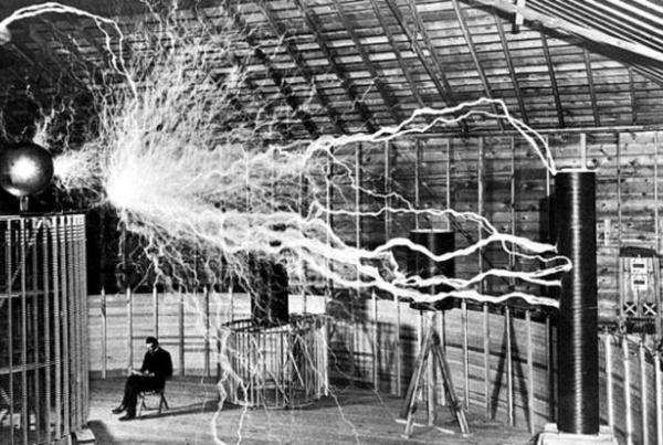 صورة لتسلا جالساً في مختبره في كولورادو سبرنجز مع جهازه المرسل المكبر (magnifying transmitter) والذي ينتج ملايين الفولتات. حقوق الصورة: Wikipedia Commons/Century Magazine/Dickenson V. Alley