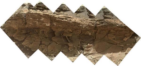 """نتوء صخري يُطلق عليه اسم ميسولا """"Missoula"""" بالقرب من ممر مارياس على سطح المريخ، ويظهر على شكل فسيفساء التقطتها آلة تصوير المريخ في المركبة كيريوستي. الأحجار الطينية الباهتة والتي تظهر في الجزء السفلي تلتقي مع الحجارة الرملية الخشنة في الأعلى في هذه المنطقة الجيولوجية التي أثارت اهتمام علماء المريخ.   تعود ملكية الصورة لـ: NASA/JPL-Caltech/MSSS"""
