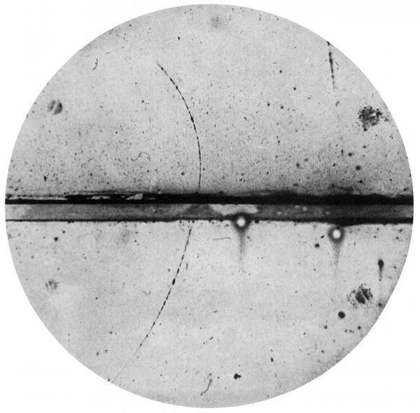 تُوضح هذه الصورة، التي التقطها عالم الفيزياء الأمريكي كارل اندرسون عام 1932، المسار الذي تركه أول بوزيترون تم التعرف عليه، والخطُّ الموجود في المركز يُمثل صفيحة من الرصاص بسماكة 6 ميليمتر تفصل بين النصفين العلوي والسفلي للحجرة. Credit: Wikimedia Commons