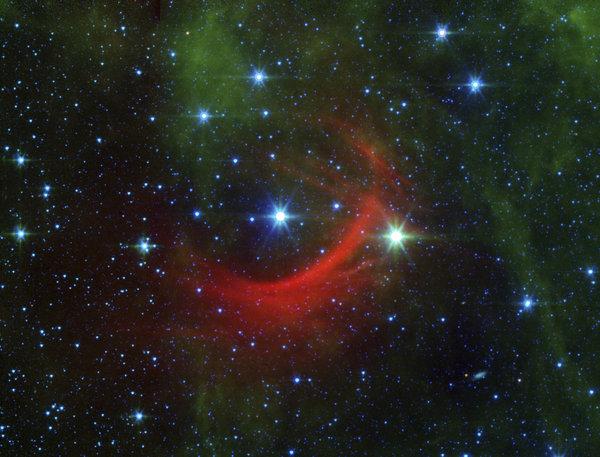 النجم السريع كابا كاسيوبيا، أو HD 2905، في الوسط، كما يمكنكم رؤية الموجة الصدمية التي نشأت عندما اصطدمت الحقول المغناطيسية ورياح الجسيمات المتدفقة من النجم بالغبار المنتشر غير المرئي بالعادة الذي يملئ الفراغ بين النجمي. حقوق الصورة: NASA/JPL-Caltech via AP