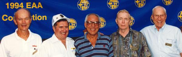 """محاطاً بطياري وحدة أبولو (من اليسار): مايكل كولنز Michael Collins (أبولو 11)، ريتشارد غوردن Richard Gordon (أبولو 12)، ستيورات روزا Stuart Roosa (أبولو 14)، وآلفرد ووردن Alfred Worden (أبولو 15)، في احتفال """"تحية لأبولو"""" عام 1994 في أوسكوش، ويسكونسن."""