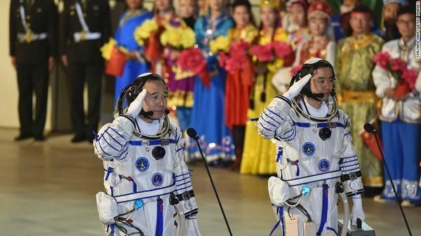 صورة لرائد الفضاء جيني هايبن Jing Haipeng (على اليسار) ورائد الفضاء سيي دو Chen Dong أثناء تأديتهما للتحية خلال مراسم إرسالهما في مهمة شنخاو11 (Shenzhou-11) الفضائية المأهولة من مركز جي كويان Jiuquan لإطلاق الأقمار الصناعية في مدينة جي كويان ، الصين.