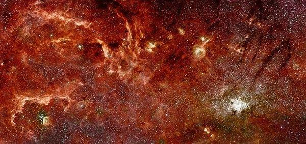 تُظهر هذه الصورة الملتقطة من تلسكوبي هابل وسبيتزر الفضائيين مركز مجرتنا على مسافة 300 سنة ضوئية كما كانت أعيننا ستراها لو كان بإمكاننا رؤية الأشعة تحت الحمراء. وتُظهر الصورة عناقيد نجمية هائلة الكتلة ودوامات من السُحُب الغازية. المصدر: (NASA, ESA, JPL, Q.D. Wang, and S. Stolovy (via Wikipedia.