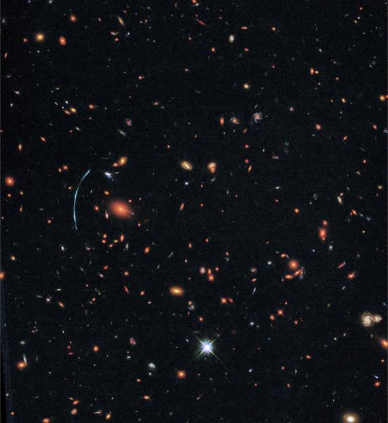 يبعد العنقود SDSS J1110+6459 حوالي ستة مليارات سنة ضوئية عن كوكبنا ويحوي مئات المجرات. ويتوضع على يسار الصورة قوس أزرق مميز يتألف من ثلاثة صور منفصلة ما هي إلا لمجرة أبعد، تدعى بالمجرة SGAS J111020.0+645950.8. وقد تم تكبير الصورة وتعديلها وتعددها بواسطة فعل جاذبية العنقود المجري بعملية سميناها أثر العدسة الثقالي.