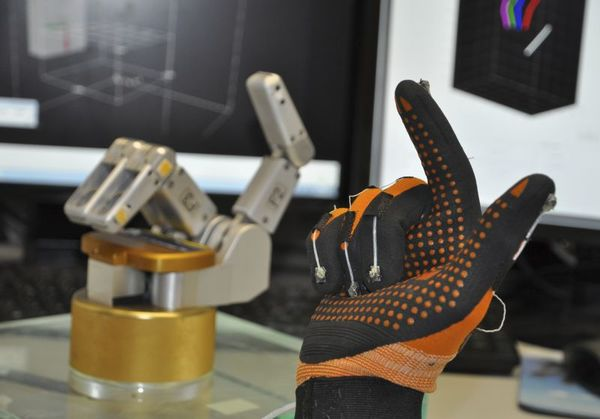 تجربة في DPZ: قفاز بيانات مع بنان مغناطيسية يقيس حركات يد المشاركين في التجربة وينقلها إلى يد روبوتية. حقوق الصورة: Stefan Schaffelhofer.