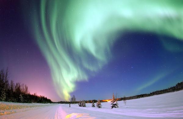 تُعرف الأضواء الشمالية (northern lights) باسمها الرسمي وهو الشفق القطبي، وهي ناتجة عن التفاعل الحاصل بين الرياح الشمسية والحقل المغناطيسي للأرض. مصدر الصورة: كارل تيت space.com .