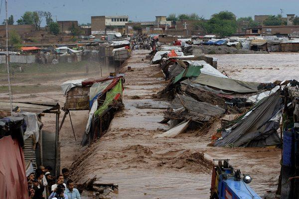 يقف القرويين خارج منازلهم خلال الفيضانات المفاجئة على مشارف بيشاور، باكستان، في نيسان/أبريل 2016. تصوير: محمد سجاد/لصالح أسوشيتد برس AP