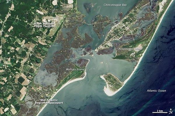 تتراجع حواجز الشواطئ الموجودة بالقرب من منشأة والوبس للطيران والميناء الفضائي الإقليمي في منطقة وسط الأطلسي، بمقدار 12 قدم في كل سنة. (صورة المرصد الأرضي التابع لوكالة ناسا بواسطة جيسي آلن Jesse Allen، وذلك باستخدام بيانات لاندسات من منظمة المسح الجيولوجي الأميركية)