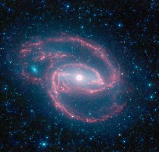 صورة لمجرةٍ مُلتفّة التقطها تلسكوب سبتزر الفضائي Spitzer Space Telescope التابع لوكالة ناسا يظهر في وسطها شيءٌ يُشبه العين. هذه العين هي ثُقب أسود عملاق تُحيط به حلقة من النجوم.  المصدر: وكالة ناسا/مختبر الدفع النفاث- معهد كاليفورنيا للتكنولوجيا