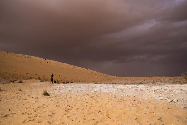 سحابة داكنة تظلّل الأفق بينما يقوم علماء الآثار بمسح موقع الوسطى ورسم خرائط له. المصدر: كلينت جانيوليس Klint Janulis