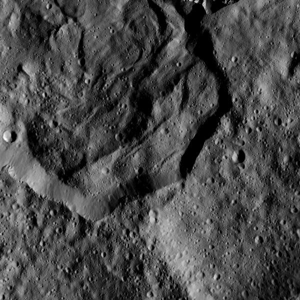 صورة ملتقطة بمركبة داون وتظهر جزءاً من فوهة ميسور Messor Crater التي يبلغ اتساعها 25 ميلاً (40 كيلومتراً)، وتقع في على ارتفاع متوسطٍ في الشمال من كوكب سيريس، ويبيّن هذا المشهد الفوهة القديمة والتي تشبه الفلقة الكبيرة وتمتدّ لتغطي نسبياً الجزء الشمالي من أرضية الفوهة، وهذا الامتداد (التدفق) هو كتلة من المواد التي تقذف عندما تشكّلت فوهة حديثة في شمالي الحافة تماماً. مصدر الصورة: NASA/JPL-Caltech/UCLA/MPS/DLR/IDA