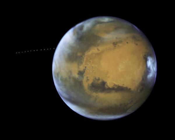 علي مدى 22 دقيقة، ألتقط هابل 13 صورة مختلفة بتقنية التعريض الطويل، مما سمح لعلماء الفلك بصنع صورة بتقنية الزوال الزمني ليوضح حركة القمر فوبوس خلال مداره (النقطة البيضاء) حول المريخ، وتلك الصورة مكونة من صور ذات تعريض طويل مختلفة اخذها مقراب ناسا الفضائي هابل عن طريق اجهزته WFC3/UVIS ،  المصدر : ناسا، وكالة الفضاء الأوربية، معهد علوم تلسكوب الفضاء وشكر موجه لـ ج.بيل ( جامعة اريزونا) و م. ولف (معهد علوم الفضاء)