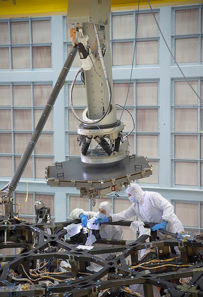 هذه الصورة ملتقطة داخل حجرة عملاقة نظيفة ومُعقّمة في مركز غودارد لرحلات الفضاء في غرينبيلت بولاية ماريلاند، حيث نرى فيها فريق عمليات تلسكوب جيمس ويب الفضائي وهو يُنهي استعداداته قُبيل البدء بعملية تركيب المرآة الأولى على هيكل التلسكوب.   المصدر: NASA/Chris Gunn