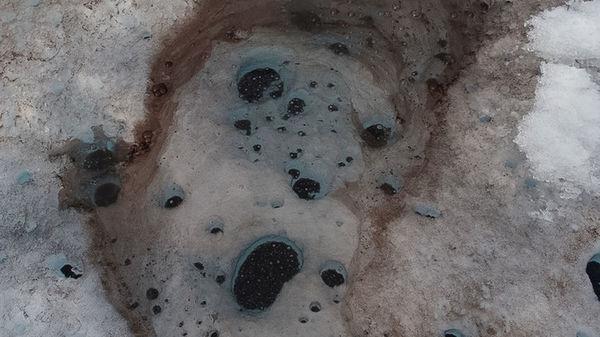 مخاريط الغبار الدقيق التي تحفر الجليد، وتكون مليئة بمادة لزجة سوداء تصبح أكثر تركيزاً بمرور كل سنة من الذوبان المصدر: آدام لي ونتر. سلاح الهندسة في الجيش الأمريكي. مركز البحوث والتطوير الهندسي معمل هندسة وأبحاث المناطق الباردة (CRREL)